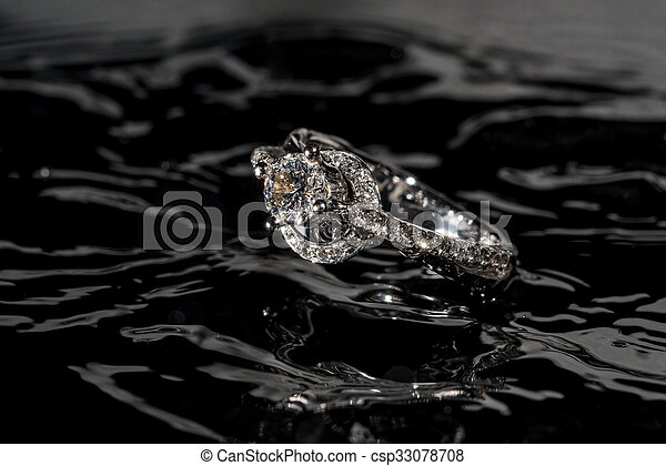 Diamond engagement ring floating in the water - csp33078708