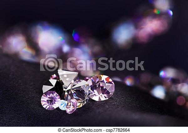 Diamond (small purple jewel) stones heap over black silk cloth background - csp7782664