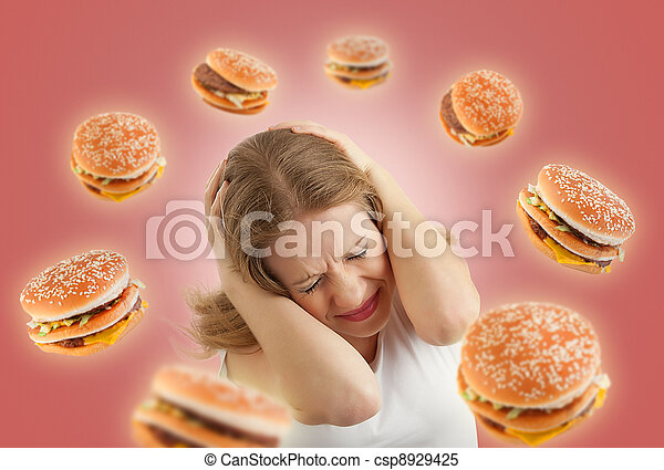 diet concept. frightened girl in the stress and flying around the burgers on a red background - csp8929425