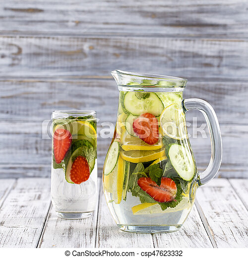 Dietary detox drink with lemon juice, red strawberry, cucumber and mint  leaves in clear water with ice