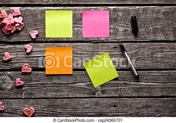 Different color sticky notes on wood table. - csp24365701