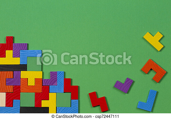 Different colorful shapes wooden blocks on green background. Top view - csp72447111
