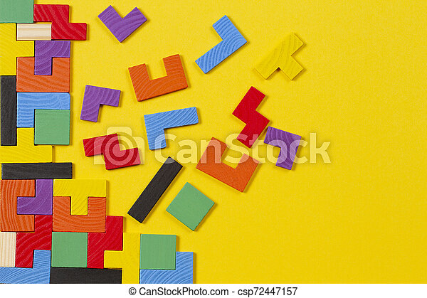 Different colorful shapes wooden blocks on yellow background. Top view - csp72447157