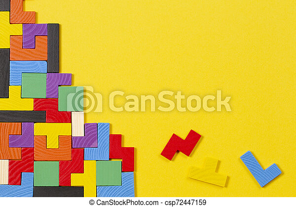 Different colorful shapes wooden blocks on yellow background. Top view - csp72447159