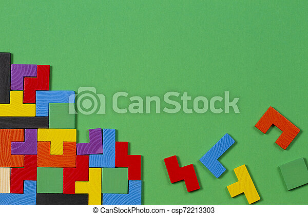 Different colorful shapes wooden blocks on green background. Top view - csp72213303