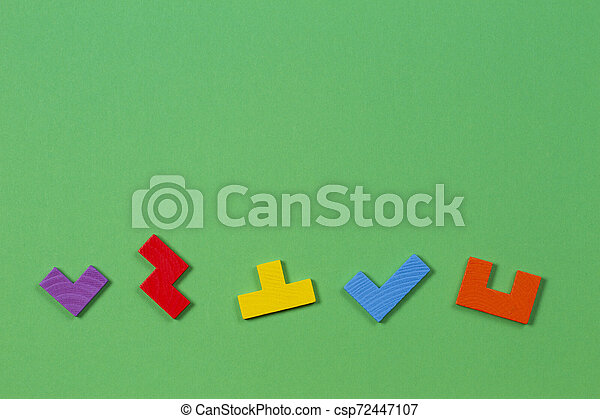 Different colorful shapes wooden blocks on green background. Top view - csp72447107