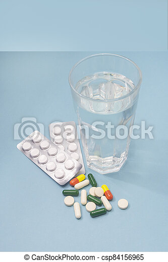 Different tablets and capsules of medicines for treatment of disease. Glass with water on blue background close-up. Selective focus - csp84156965