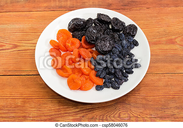 Different traditional dried fruits on dish on old rustic table - csp58046076