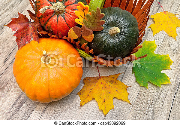 Different types of pumpkins and autumn leaves on a wooden table - csp43092069