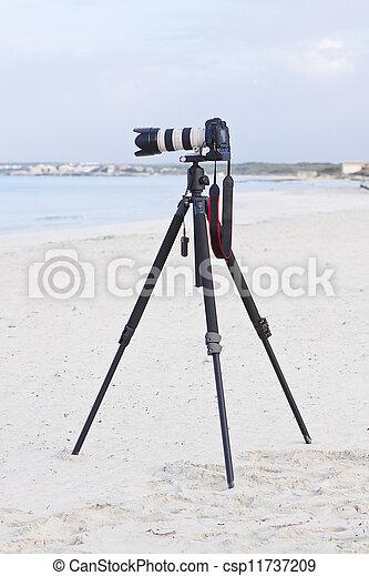 digital slr camera on tripod on beach in summer - csp11737209