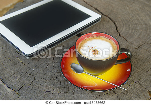 digital tablet and coffee cup on wooden table - csp18455662
