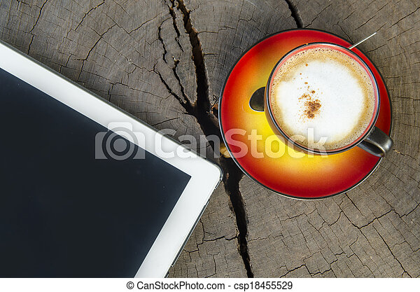 digital tablet and coffee cup on wooden table - csp18455529