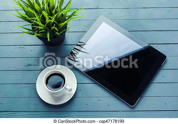 digital tablet and coffee cup on wooden table - csp47178199