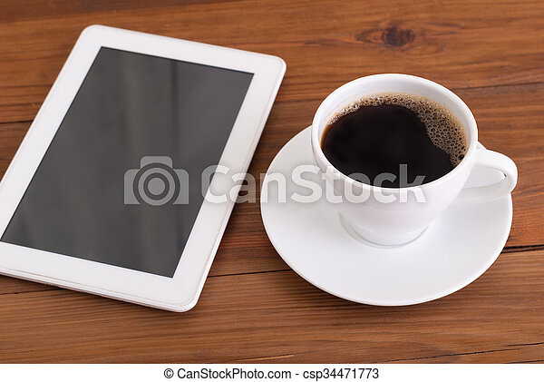 Digital tablet and cup of coffee on wooden desk. - csp34471773