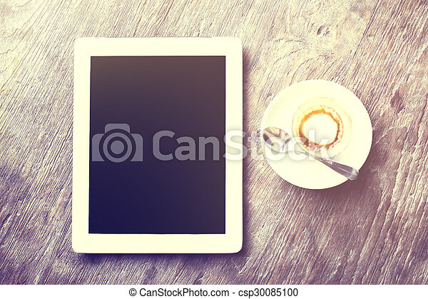 Digital tablet with cup of coffee on a wooden table - csp30085100