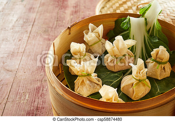 Dim sum dumplings with cabbage in bamboo basket - csp58874480