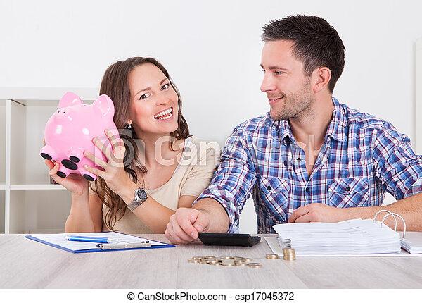 Una pareja ahorrando dinero - csp17045372