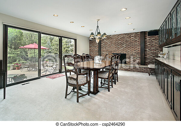 Dining Room With Brick Fireplace And View To Patio
