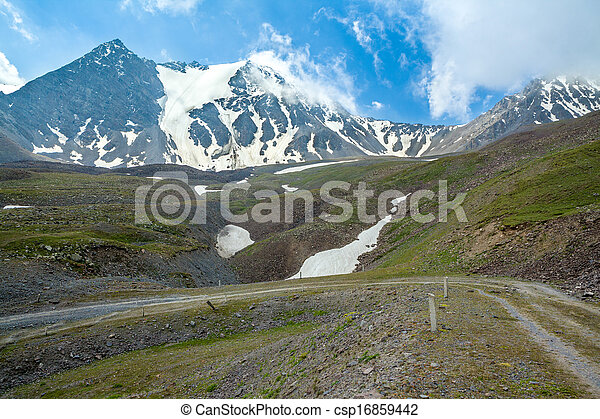 Dirt road in high snowy mountains - csp16859442