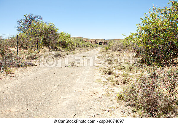 Dirt road on farm in arid region - csp34074697