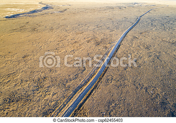 Dirt road winding through prairie in northern Colorado - csp62455403
