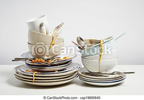 Dirty dishes pile needing washing up on white background - csp19690640