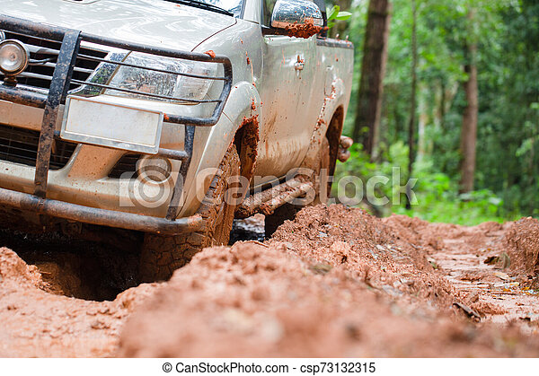 Dirty offroad car, SUV covered with mud on countryside road, Off-road tires, offroad travel and driving concept. - csp73132315