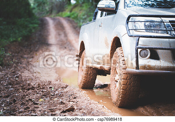 Dirty offroad car, SUV covered with mud on countryside road, Off-road tires, offroad travel and driving concept. - csp76989418