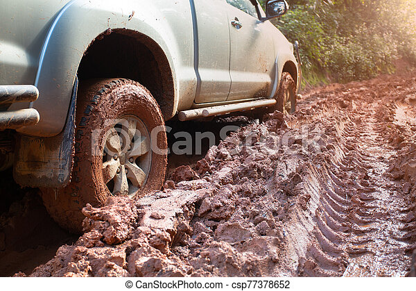 Dirty offroad car, SUV covered with mud on countryside road, Off-road tires, offroad travel and driving concept. - csp77378652