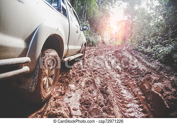 Dirty offroad car, SUV covered with mud on countryside road, Off-road tires, offroad travel and driving concept. - csp72971226
