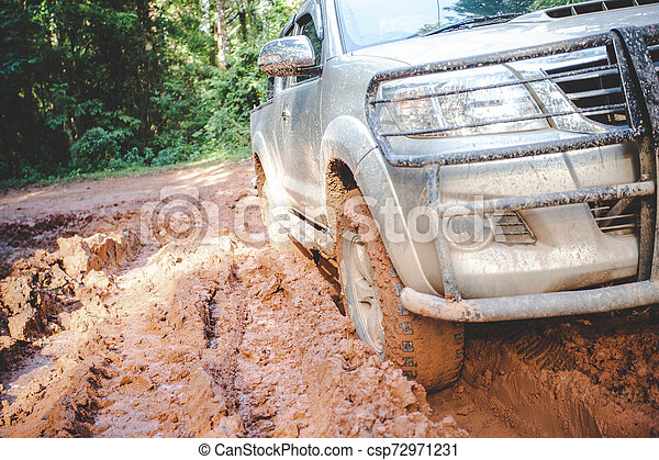 Dirty offroad car, SUV covered with mud on countryside road, Off-road tires, offroad travel and driving concept. - csp72971231