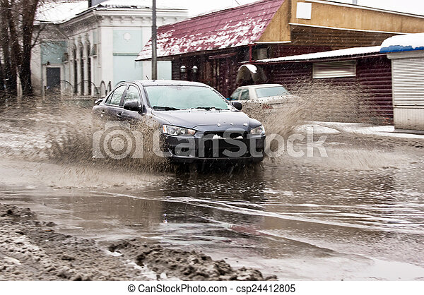Dirty water splash from the car wheels at spring snowy street - csp24412805