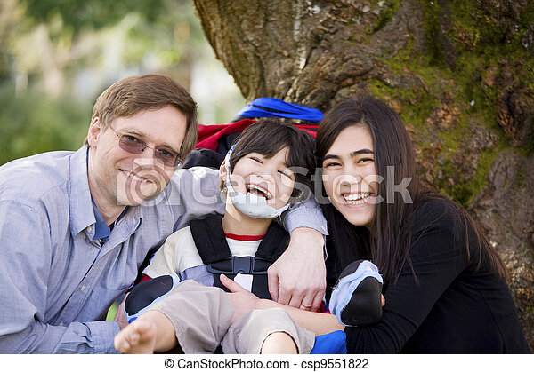 Disabled boy in wheelcahir surrounded by father and sister - csp9551822