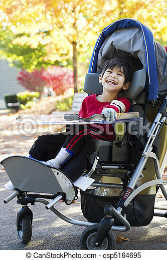 Disabled boy with cerebral palsy in medical stroller enjoying an autumn day outdoors at the park - csp5164695