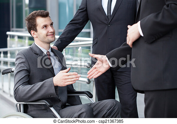 Disabled businessman shaking hand with business partners - csp21367385