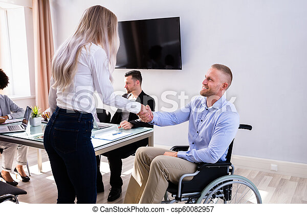 Disabled Businessman Shaking Hand With His Colleague - csp60082957