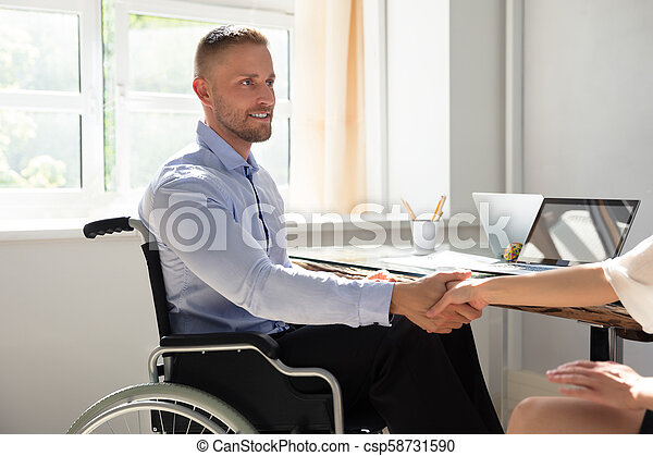Disabled Businessman Shaking Hand With His Partner - csp58731590
