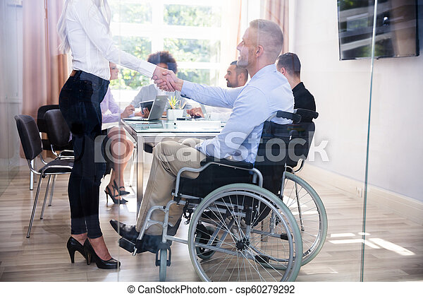 Disabled Businessman Shaking Hand With His Colleague - csp60279292