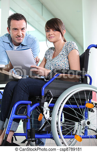 Disabled female office worked with colleague - csp8789181