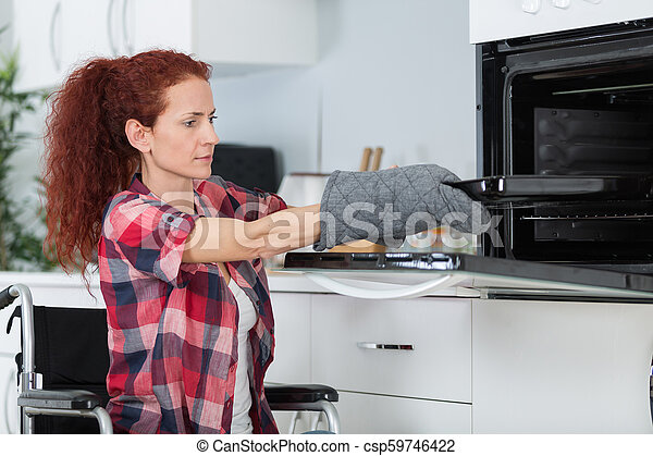 disabled independant woman in wheelchair preparing meal in kitchen - csp59746422