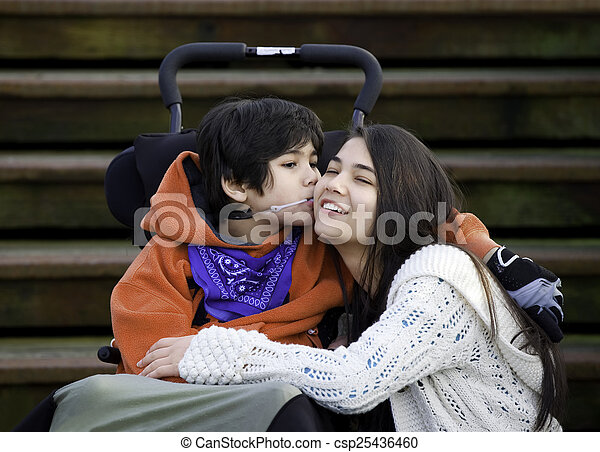 Disabled little boy kissing his big sister on cheek while seated - csp25436460
