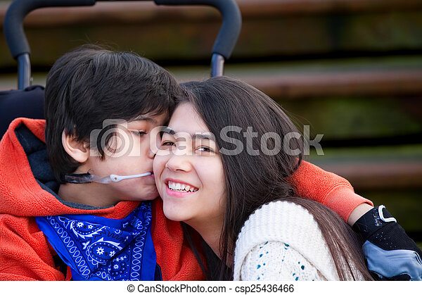 Disabled little boy kissing his big sister on cheek while seated - csp25436466