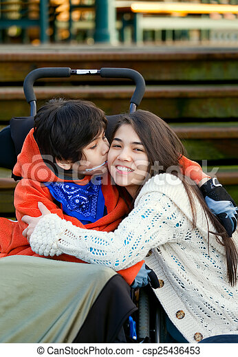 Disabled little boy kissing his big sister on cheek while seated - csp25436453