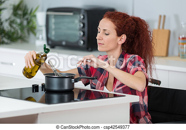 disabled woman cooking in her kitchen - csp42549377