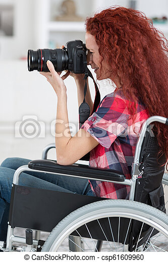disabled woman in wheelchair have a passion for photography - csp61609960