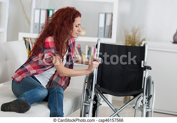 disabled woman trying to sit on wheelchair - csp46157566