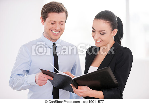 Discussing contract. Young man and woman in formalwear discussing something while holding folder with documents - csp19011577