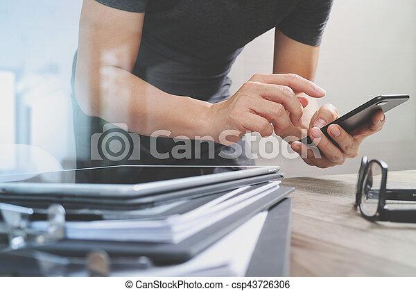 Diseñador de mano usando pagos móviles en internet, omni Channel, en la oficina moderna de madera, en pantalla de interfaz gráfica, gafas, filtro - csp43726306