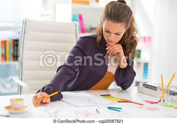 Diseñadora de moda pensativa trabajando en la oficina - csp20087921