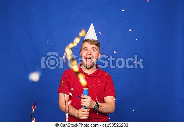 Un joven gracioso con confeti. Fiestas, carnaval, Navidad y el concepto de fiesta de Año Nuevo - csp50526233